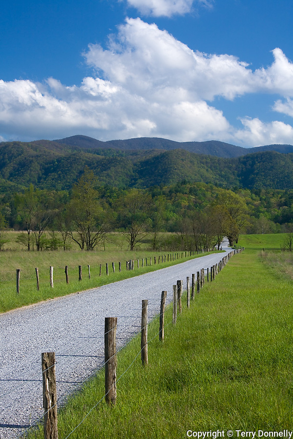 Great Smoky Mts. National Park, TN/NC<br /> Wood fence posts line Hyatt lane in Cades cove with white clouds hovering over the ridges of the Smoky Mountains