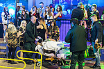 © Joel Goodman - 07973 332324 . 27/12/2016 . Wigan , UK . People watch as a woman is wheeled on a trolley on to the back of an ambulance . Revellers in Wigan enjoy Boxing Day drinks and clubbing in Wigan Wallgate . In recent years a tradition has been established in which people go out wearing fancy-dress costumes on Boxing Day night . Photo credit : Joel Goodman