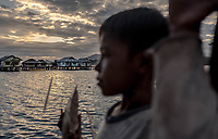 A Bajau boy holds onto a model boat as the sun sets over the stilt village of Kabalutan, Indonesia. (Photo: Aurélie Marrier d'Unienville)
