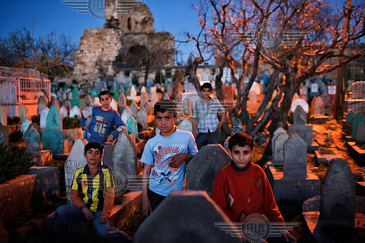 Children in the city cemetery, beneath the ancient city walls which date from 400 BC. In this cemetery, up to 1,000 victims of violence during the 1990s are buried. During that time Hezbollah (Hizbollah) guerrillas, the PKK (Kurdistan Worker's Party) and the Turkish military and police intelligence services were all active in the area, and there were a large number of unsolved murders.