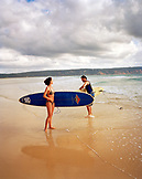 AUSTRALIA, Queensland, Noosa Heads, a man and woman prepare to enter the water, 40 Mile Beach