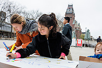Laila Ozat-McIntyre, 7, of Malden, Mass., (center), and Ayse Yemiscigil, 28, makes signs for the March for Science demonstration in Harvard University's Science Center Plaza in Cambridge, Massachusetts, on Sat., April 22, 2017. Ozat-McIntyre's father is a student at Harvard's Graduate School of Education. Yemiscigil is from Turkey and says she will next year be a Visiting Fellow PhD student studying Behavioral Science at Harvard.