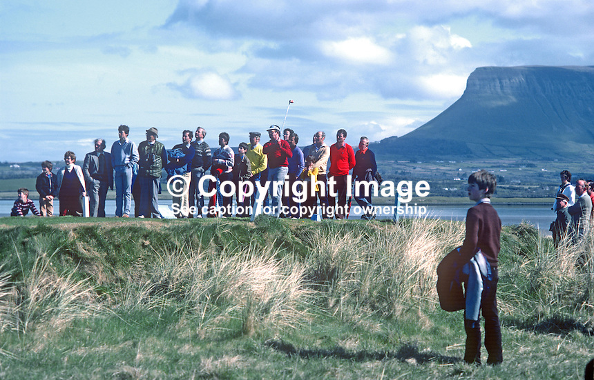 West of Ireland Amateur Open Golf Championship at the spectacular County Sligo Golf Club course at Rosses Point, Co Sligo. Spectators watch a competitor tee off at the 12th with Ben Bulben in the background. 19820600107b..Copyright Image from Victor Patterson, 54 Dorchester Park, Belfast, UK, BT9 6RJ.  Tel: +44 28 90661296  Mobile: +44 7802 353836.Email: victorpatterson@me.com Email: victorpatterson@gmail.com..For my Terms and Conditions of Use go to http://www.victorpatterson.com/ and click on Terms & Conditions
