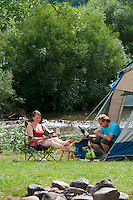 Nahemuhle, Monzingen, Rheinland Pfalz, Germany, July 2010. A family is camping in their tent and bbq-ing on an open fire next to the river.Camping Nahemuhle is situated on the banks of the River Nahe. Monzingen is a municipality in the district of Bad Kreuznach in Rhineland-Palatinate, in western Germany. Founded over 1200 years ago the village contains a number of historic buildings. The fertile river valleys and the rolling hills form the basis for some of Germany's best wines.  Photo by Frits Meyst / Adventure4ever.com