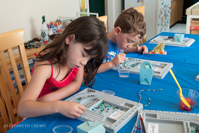 Berkeley CA Girl, Chinese, age seven and boy, six, concentrating on bead designing project at birthday party  MR