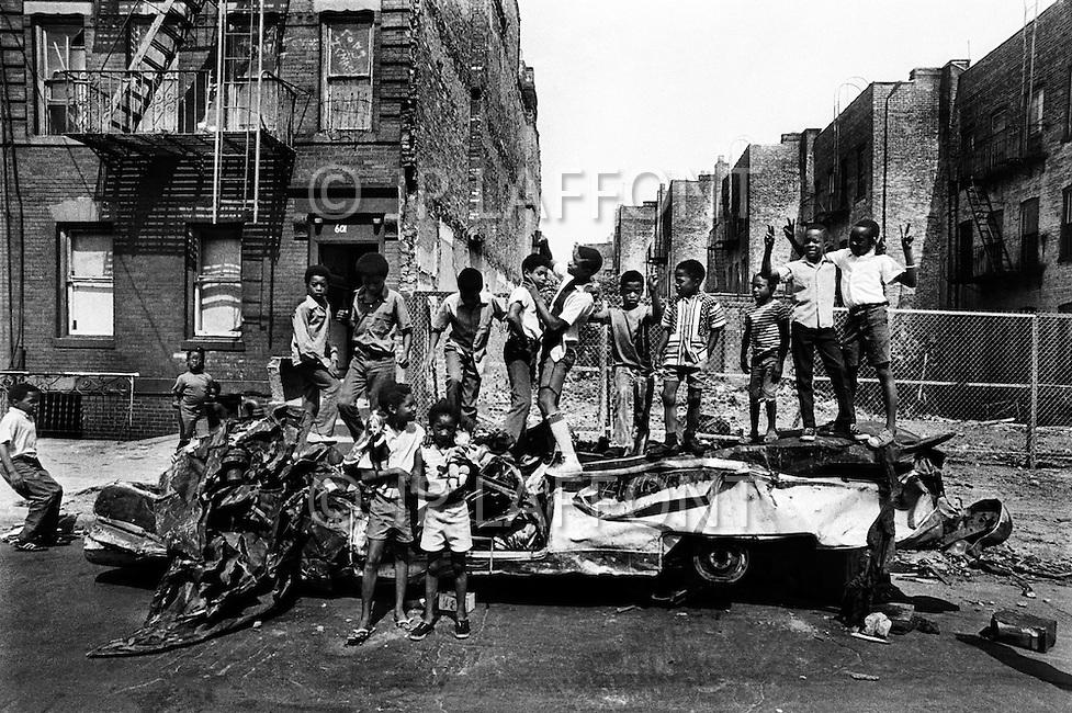 Brooklyn, New York City, NY - August, 1971<br /> Kids pose atop a destroyed car on hot summer day. The city&rsquo;s outer-boroughs bore the brunt of the city&rsquo;s increasing financial problems. The borough became a wasteland of burned-out buildings, abandoned cars and trash. All of which became a playground for the city&rsquo;s youth. <br /> Brooklyn, New York City, NY. Aout, 1971. <br /> Un ch&acirc;ssis de voiture d&eacute;labr&eacute; devient le terrain de jeux pour les enfants de ce ghetto.  Ils ne manquent pas d&rsquo;imagination et les filles viennent y jouer avec leurs poup&eacute;es.