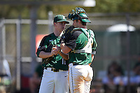 Dartmouth Big Green relief pitcher Chris Burkholder (16) talks with catcher Adam Gauthier (18) during a game against the Eastern Michigan Eagles on February 25, 2017 at North Charlotte Regional Park in Port Charlotte, Florida.  Dartmouth defeated Eastern Michigan 8-4.  (Mike Janes/Four Seam Images)