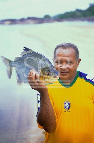 Tataquara, Brazil. Antonio, a local guide, wearing a Brazil football shirt holding a pacu fish.