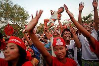 A man lifts a child as supporters of Aung San Suu Kyi and her National League for Democracy sing and dance during a campaign rally in Yangon March 30, 2012. Myanmar holds by-elections on Sunday and Suu Kyi is standing for one of 45 parliamentary seats to be filled. REUTERS/Damir Sagolj (MYANMAR)