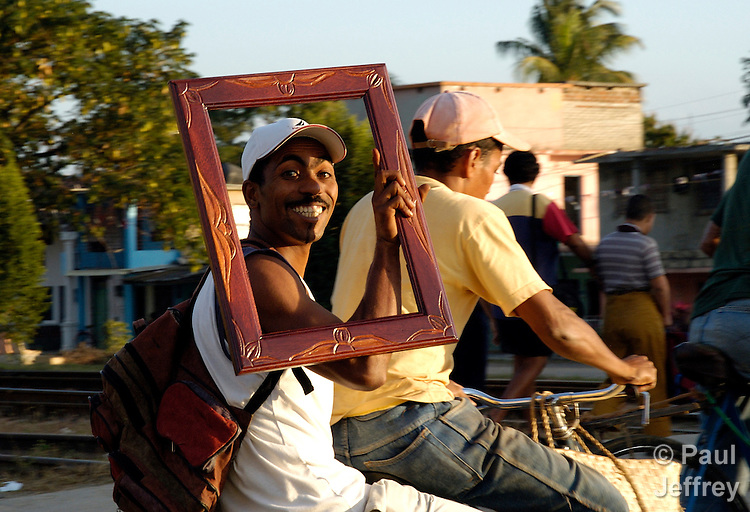 In the Cuban city of Ciego de Avila, a bicycle passenger frames his smile.