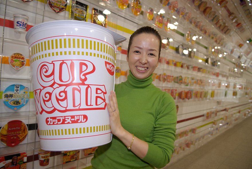 Yoshie Kawate, a spokeswoman for the Instant Ramen Museum, holds a giant inflatable cup noodle. The wall behind her shows some of Nissin's hundreds of instant noodle products over the years.The Instant Ramen Museum in Ikeda, near the Japanese city of Osaka, has welcomed some 2 million visitors over the years. .
