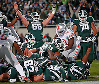 Michigan State Spartans running back Jeremy Langford (33) scores a rushing touchdown against Ohio State Buckeyes defense during the 2nd quarter at Spartan Stadium in East Lansing, Michigan on November 8, 2014.  (Dispatch photo by Kyle Robertson)