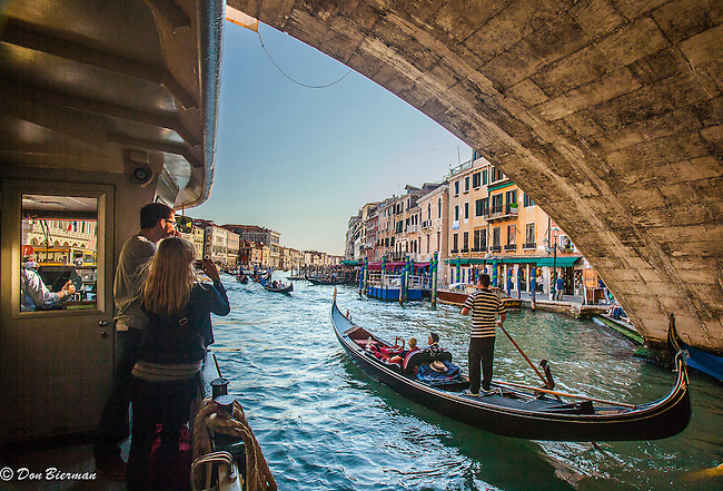 Venice: Regatta Day, decorated boats of every kind passing under the Rialto Bridge on the Grand Canal. Venice, Italy