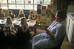 Village junior school lunch time break. Lunch Hour. School teacher reading to children after lunch. Sapperton Gloucestershire 1980s