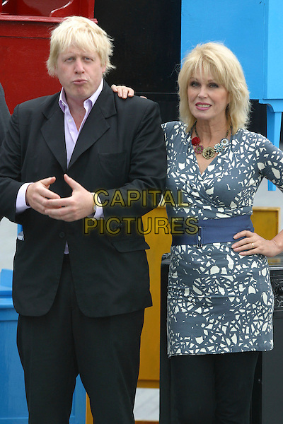 BORIS JOHNSON (Mayor of London) & JOANNA LUMLEY.The launch of the old furniture recycling scheme, The Scoop, More London, the Queen's Walk, London, England. .July 12th, 2010 .half length black suit grey gray white print top blue waist belt trousers hands.CAP/JEZ.©JEZ/Capital Pictures.