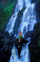 Woman sitting by the waterfalls in Waipio Valley