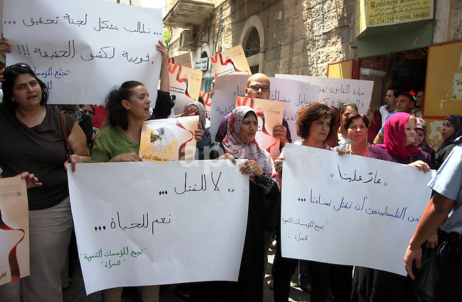 Palestinian women hold signs during a demonstration protesting violence against women held at the spot where a woman's throat was allegedly slashed by her husband on Monday, in the West Bank town of Bethlehem, Wednesday, Aug. 1, 2012. Dozens of activists called on police and courts to do more to protect women against abusive husbands. Palestinian President Mahmoud Abbas has promised to end a long-standing practice of treating killings in the family 'with leniency. However, violence against women continues to be tolerated in Palestinian society and abusive husbands are rarely punished. Photo by Issam Rimawi