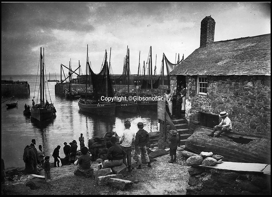 BNPS.co.uk (01202 558833)<br /> Pic: GibsonOfScilly/BNPS<br /> <br /> Mousehole in the 1890's<br /> <br /> An archive of eye-opening photographs documenting the grim reality of Poldark's Cornwall has emerged for sale for £25,000.<br /> <br /> More than 1,500 black and white images show the gritty lives lived by poverty-stricken families in late 19th and early 20th century Cornwall - around the same time that Winston Graham's famous Poldark novels were set.<br /> <br /> The collection reveals the lowly beginnings of towns like Rock, Fowey, Newquay and St Ives long before they became picture-postcard tourist hotspots.<br /> <br /> Images show young filth-covered children playing barefoot in squalid streets, impoverished families standing around outside the local tax office, and weather-beaten fishwives tending to the day's catch.<br /> <br /> The Cornish archive, comprising 1,200 original photographic prints and 300 glass negative plates, is tipped to fetch £25,000 when it goes under the hammer as one lot at Penzance Auction House.