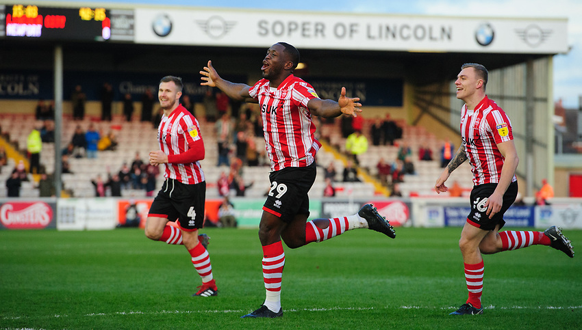 Lincoln City's John Akinde, centre, celebrates scoring the opening goal with team-mates, Michael O'Connor, left, and Harry Anderson<br /> <br /> Photographer Chris Vaughan/CameraSport<br /> <br /> The EFL Sky Bet League Two - Lincoln City v Newport County - Saturday 22nd December 201 - Sincil Bank - Lincoln<br /> <br /> World Copyright © 2018 CameraSport. All rights reserved. 43 Linden Ave. Countesthorpe. Leicester. England. LE8 5PG - Tel: +44 (0) 116 277 4147 - admin@camerasport.com - www.camerasport.com