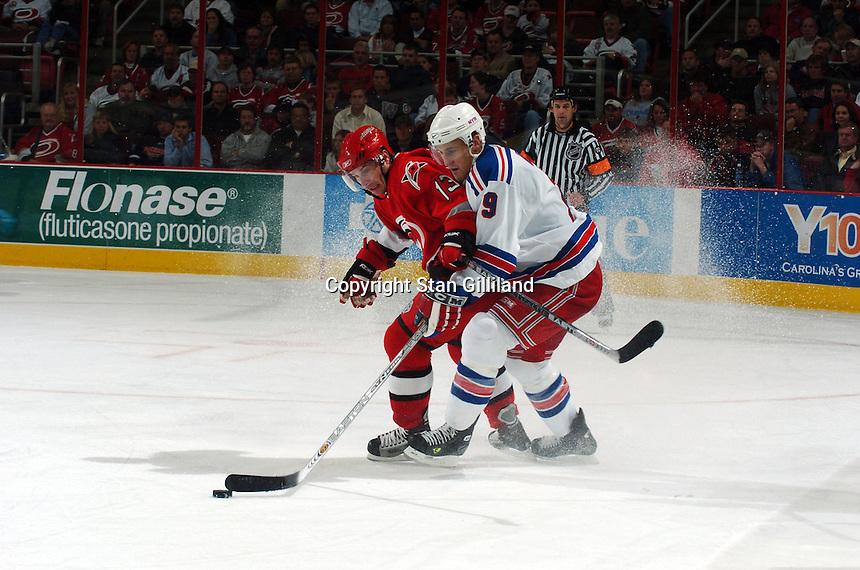 Carolina Hurricanes' Ray Whitney (13) tries to knock the New York Rangers' Blair Betts (19) off the puck during their game Thursday, Nov. 17, 2005 in Raleigh, NC. Carolina won 5-1.