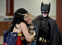 NWA Democrat-Gazette/DAVID GOTTSCHALK Miles McJunkin, 5, receives a hug from costumed superhero Wonder Woman  Thursday, March 21, 2019, as she kneels with Batman during Superhero Day at the Jones Center in Springdale. The Jones Center has held a variety of different activities daily during Spring Break. Friday will feature the princesses from the animated film Frozen during Frozen Friday on the ice skating rink at the center.