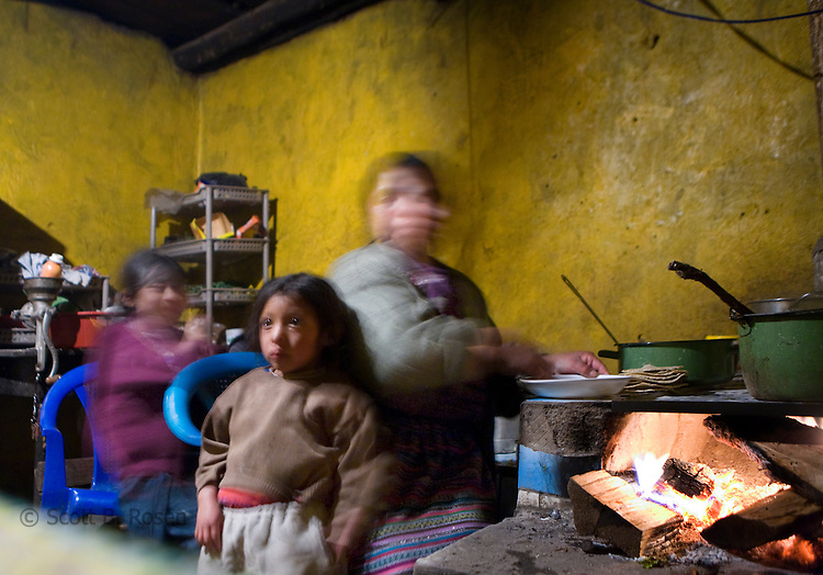 Guatemalan woman prepares tortillas in her kitchen with her two daughters