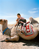 MONGOLIA, Nemegt Basin, a boy and his camel take a rest, the Gobi desert