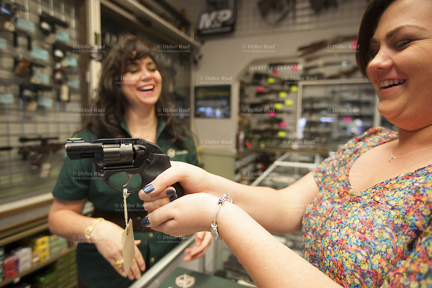 USA. Arizona state. Avondale town. Cheryl Todd (L) is the owner and the manager of the gun shop AZFirearms.com with over 1'000 guns in stock. She stands behind the store's counter and laughs while advising a smiling young woman interested in buying a handgun for her personal protection. The woman holds a pistol Ruger LCR 9mm in both her hands. The Ruger is a light carry revolver to fit a concealed carry holster. The woman wears on her left wrist a silver bracelet with an american flag. A firearm is a portable gun, being a barreled weapon that launches one or more projectiles often driven by the action of an explosive force. Most modern firearms have rifled barrels to impart spin to the projectile for improved flight stability. The word firearms usually is used in a sense restricted to small arms (weapons that can be carried by a single person). The right to keep and bear arms is a fundamental right protected in the United States by the Second Amendment of the Bill of Rights in the Constitution of the United States of America and in the state constitutions of Arizona and 43 other states. 25.01.16 © 2016 Didier Ruef