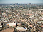 A window seat departing Phoenix, Arizona, Interstate 17 heads thorugh the middle with the  Phoenix Mountains at the top.
