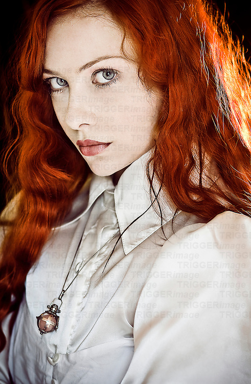 A girl with red hair staring directly into the camera wearing a white shirt and a long necklace.