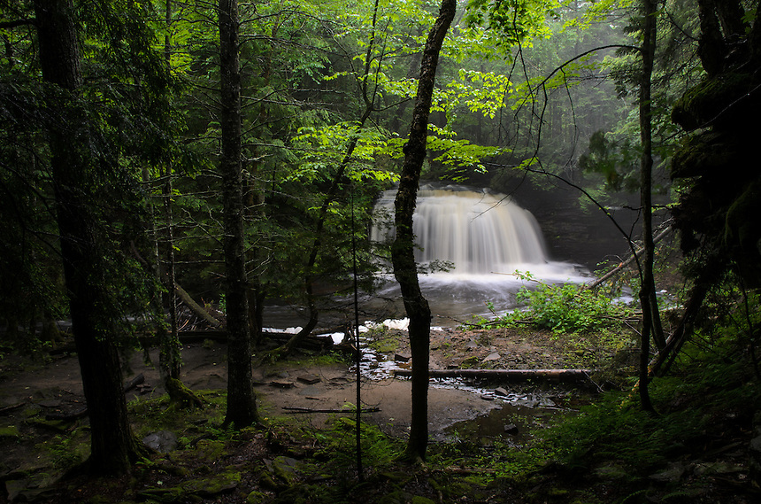 An enchanting view of Rock River Falls flowing through a vibrant forest. Chatham, MI