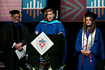 Paul Zionts, dean of the College of Education, left, looks on as Kathryn A. Kaysen Jackson, Class of 1997, center, reads the alumni induction with Virginia R. McElwain, student speaker, right, Saturday, June 10, 2017, during the DePaul University College of Education commencement ceremony at the Rosemont Theatre in Rosemont, IL. (DePaul University/Jeff Carrion)