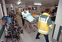 Paramedic ambulance crew rushing a casualty into the crash room of an accident and emergency department at Christmas time. This image may only be used to portray the subject in a positive manner..©shoutpictures.com..john@shoutpictures.com