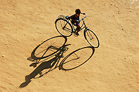 Young boy riding a huge bike and his long shadow on a sandy field, at sunset, Bagan, Myanmar Few years ago photographers Anthony Asael and Stepahnie Rabemiafara dreamed a dream that seemed quite imposible: to visit every country of the World promoting arts and tolerance among children and, of course, taking photographs of them. With little money and resources but an impressing will, the duo got an astonishing goal. In four years they visited 300 schools in 192 countries where kids participating of the project created 18,000 pieces of artwork. <br />