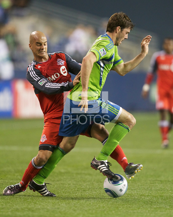 Toronto FC defender Mikael Yourassowsky steals the ball from Seattle Sounders FC forward Brad Evans during play at Qwest Field in Seattle Saturday April 30, 2011. The Sounders won the game 3-0.