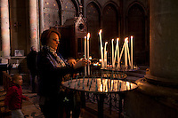 Lighting votive candles in the Sainte Therese chapel inside the cathedral of Notre-Dame de Reims, Reims, France, 11 November 2015