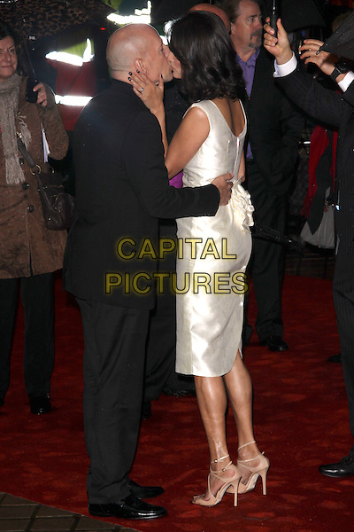 """BRUCE WILLIS & EMMA HEMING .""""Red"""" UK film premiere, Royal Festival Hall, Southbank Centre, London, England, UK, 19th October 2010. .full length suit black shirt jacket wife couple married husband pink silver sleeveless gold beige patent dress side white kissing cheek kiss side hug hugging embrace .CAP/AH.©Adam Houghton/Capital Pictures."""