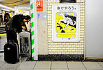 "A man digs around for discarded magazines to resell next to a poster requesting commuters refrain from lewd behavior on trains at an underground station in Tokyo, Japan. The Japanese are well known for their civility and politeness,  but a recent governmental campaign to clamp down on lewd behaviour that may inconvenienc others -- including talking on cell phones and applying makeup while commuting on a train -- was fueled by a decline in everyday etiquette and manners. The poster's headline reads ""Please do it at home."""