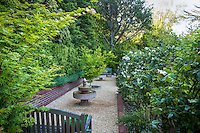 Narrow, secret garden room with  bench and fountain on pea gravel patio