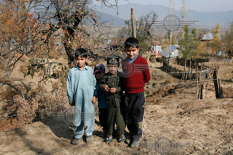"""Boy with toy gun and """"Indian"""" uniform, with friends. Dardpora is a village where many has died as a result of fighting between Indian military and Kashmiri separatists. Kashmir, India. © Fredrik Naumann/Felix Features"""