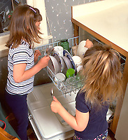 Sisters loading dishwasher after lunch ages 5 and 3.  Western Springs  Illinois USA