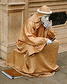 Venice, Italy - March 25, 2006 --  A street mime, who makes his money by posing as a statue for photos with tourists, takes a break to smoke a cigarette and make a call from his cell phone in Venice, Italy on March 25, 2006.  .Credit: Ron Sachs / CNP
