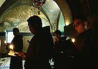 Monks and pilgrims at a service in the Armenian Orthodox Church of the Sepulchre. Jerusalem, Israel.
