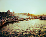 TURKEY, Istanbul, tourists outside Yeni Cami mosque and boats selling food along the Golden Horn.