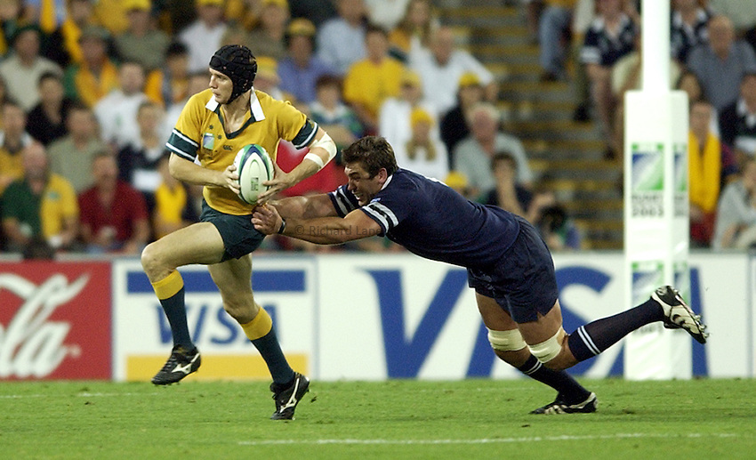 Photo: Richard Lane..Australia v Scotland.  Quarter-Final 2, at the Suncorp Stadium, Brisbane. RWC 2003. 08/11/2003..Stephen Larkham breaks away from Nathan Hines.