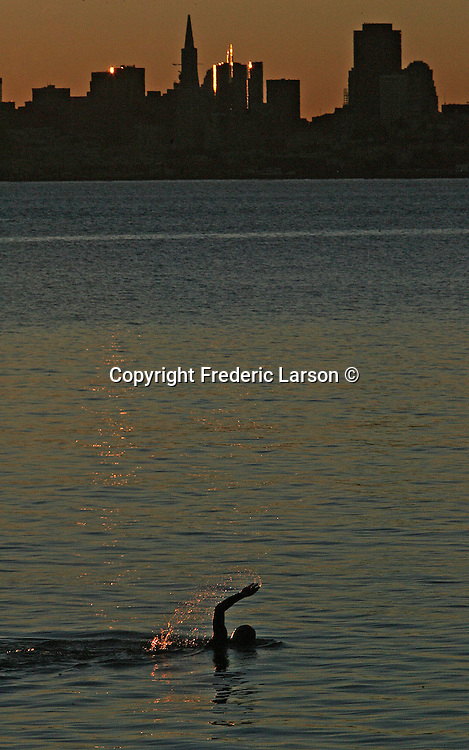 A morning swimmer does laps off the shore of Sausalito during sunrise.