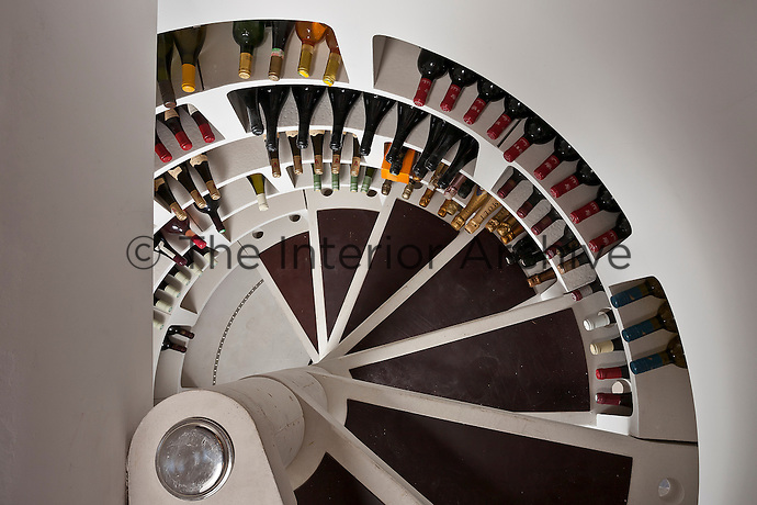 Storage bins line the spiral staircase leading down to the wine-cellar
