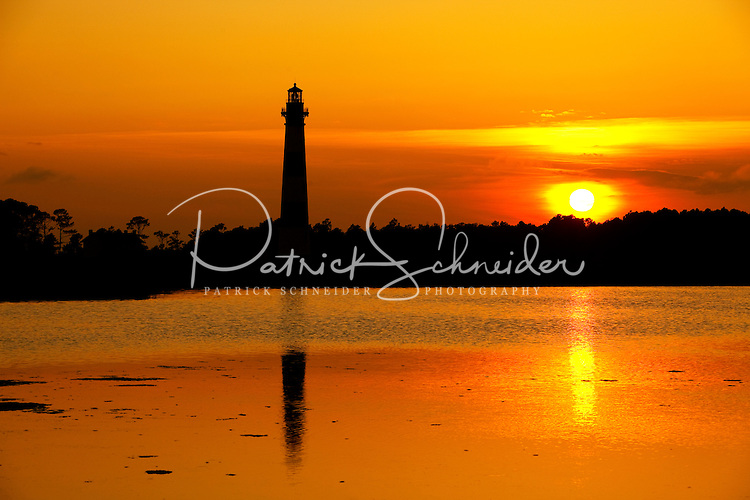 The popular Bodie Island Lighthouse reflects in the water at sunset on a clear summer day. Bodie Island Lighthouse, located on Bodie Island on North Carolina's Outer Banks, was built in 1872. It stands 156 feet tall and is located on the Roanoke Sound side of the first island that is part of the Cape Hatteras National Seashore. The lighthouse is just south of Nag's Head, a few miles before Oregon Inlet. The conical-shaped lighthouse has white and black bands with a black lantern house. Charlotte NC photographer Patrick Schneider has extensive photo collections of the following lighthouses: Bodie Island Lighthouse, Bald Head Island Lighthouse, Cape Fear Lighthouse, Cape Hatteras Lighthouse, Cape Lookout Lighthouse, Currituck Beach Lighthouse, Diamond Shoal Lighthouse, Federal Point Lighthouse, Oak Island Lighthouse, and Ocracoke Lighthouse on Ocracoke Island.