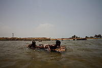 two young boys, catch mussels  in a lagoon in the Volta region, Ghana, on Saturday March 09 2007.
