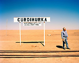 AUSTRALIA, Curdimurka, the Outback, Pilot Trevor Wright standing by signboard and railroad tracks in the outback